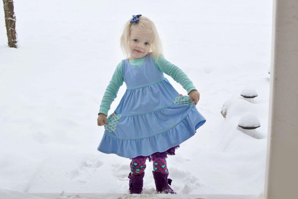 Little girl in the snow wearing a Matilda Jane dress - Mommy Scene
