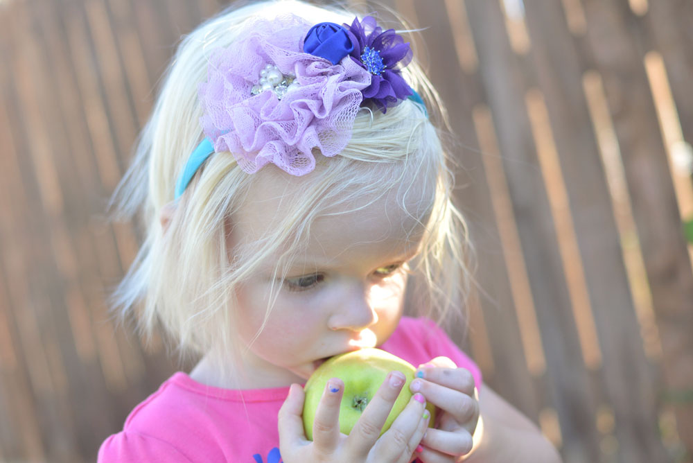 Toddler girl eating an apple - Mommy Scene