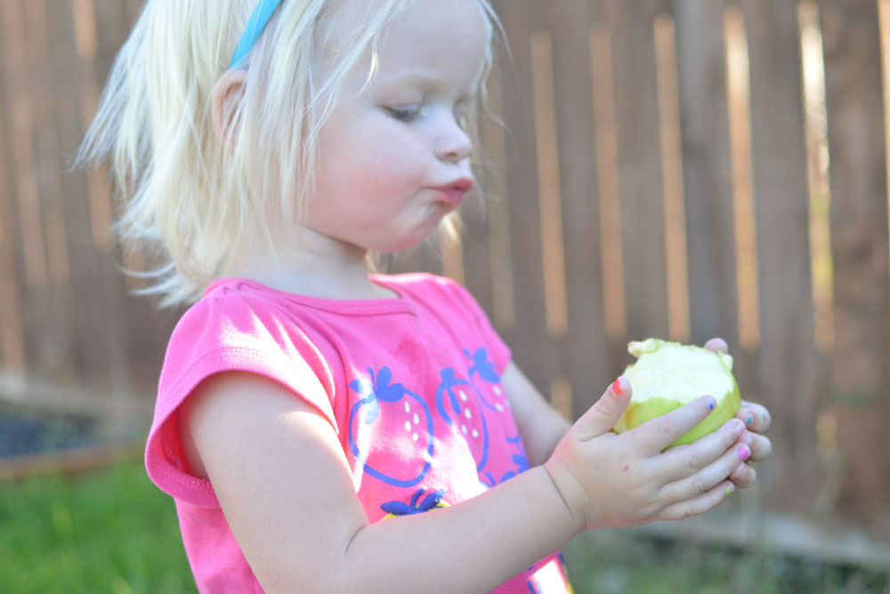 Cute toddler girl eating an apple - Mommy Scene