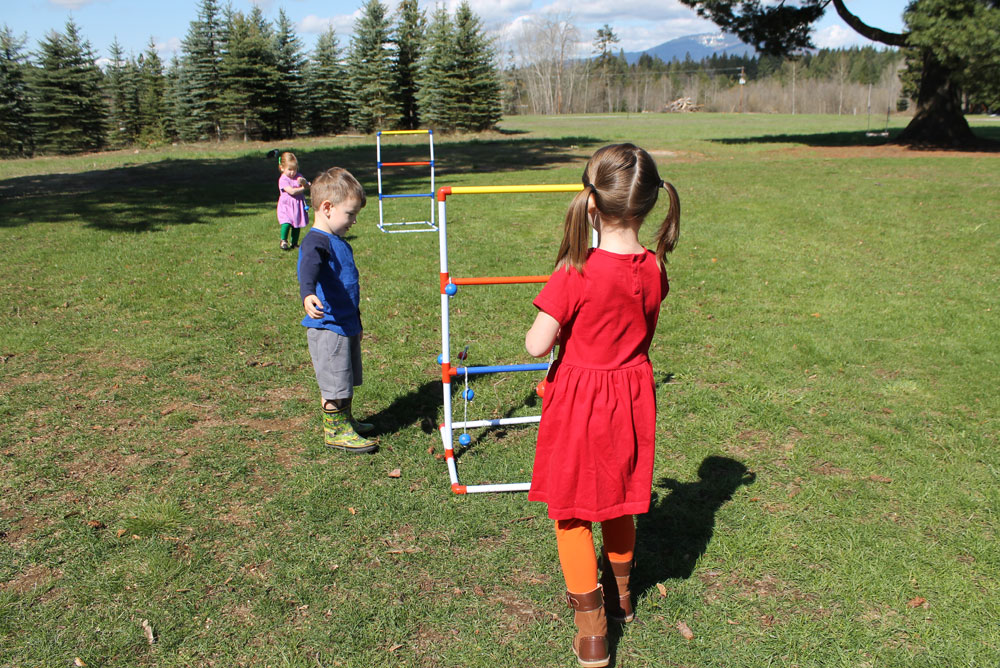 Primary Kids Clothing and playing ladder ball in the backyard - Mommy Scene