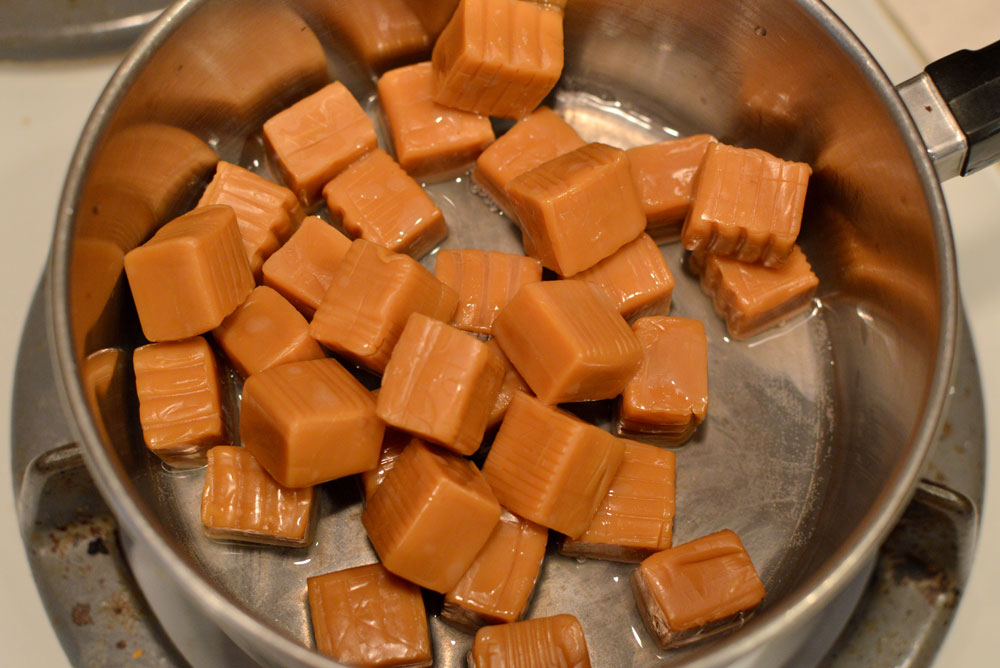 Melt caramel candies to make DIY caramel apples - Mommy Scene