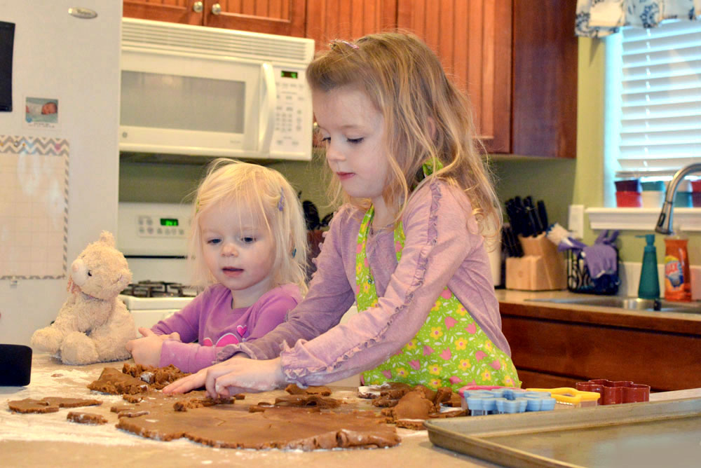 Little girls making holiday treats and gingerbread cookies