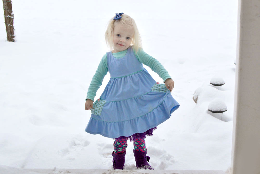 Little girl in Matilda Jane dress playing in the snow