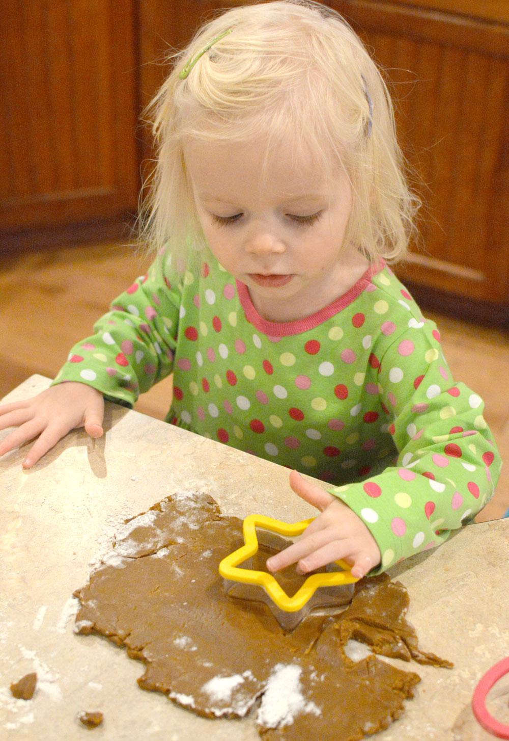 Cute little girl baking cookies wearing a Kelly's Kids dress