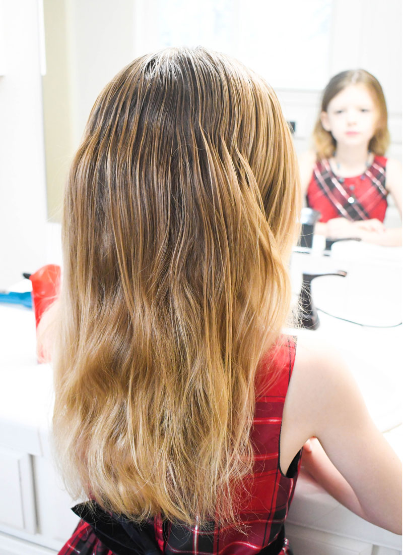 To make a bow hair style, first brush the hair straight down the back